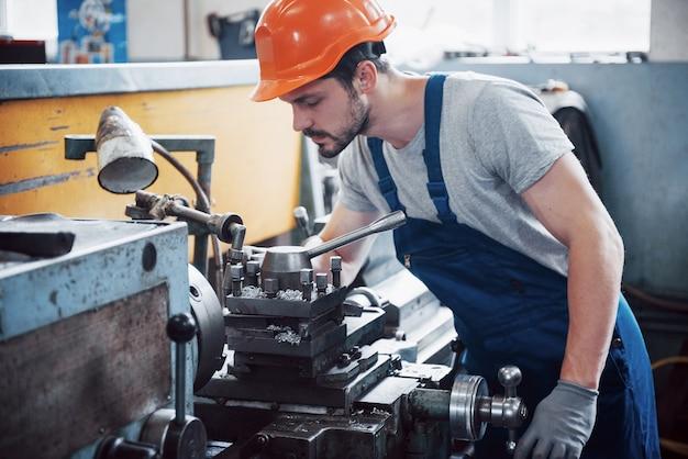 Retrato de um jovem trabalhador em um capacete em uma grande fábrica de reciclagem de resíduos.