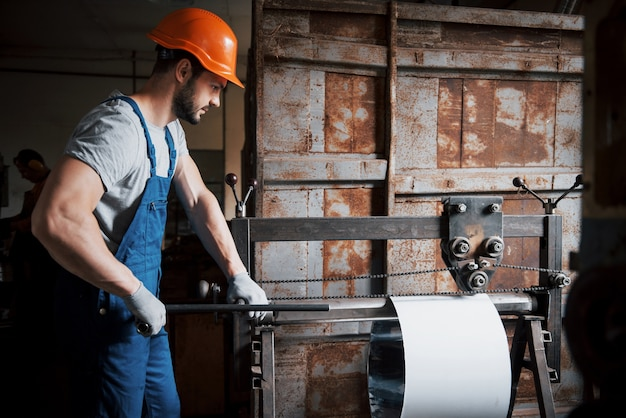 Retrato de um jovem trabalhador em um capacete em uma grande usina de metais.