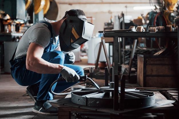 Retrato de um jovem trabalhador em uma grande usina de metal.