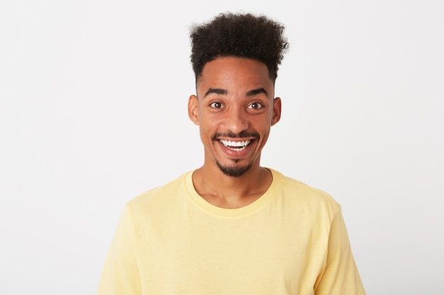 Retrato de um jovem triste e chateado com cabelo encaracolado e vestindo uma camiseta amarela parece deprimido e lábios curvos isolados sobre a parede branca