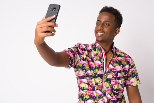 Retrato de um jovem turista africano com cabelo afro contra uma parede branca