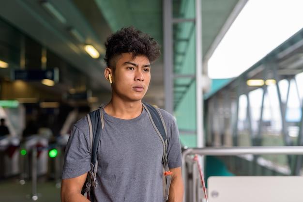 Retrato de um jovem turista asiático com cabelo encaracolado como um mochileiro vendendo tracoronavírus na estação ferroviária do céu