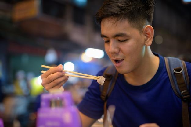 Retrato de um jovem turista asiático explorando chinatown em bangkok, tailândia