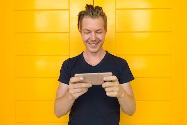 Retrato de um jovem turista bonito em frente a uma porta amarela