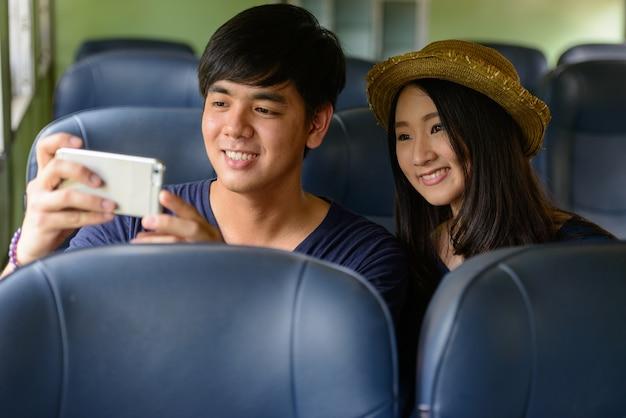 Retrato de um jovem turista filipino e uma jovem turista asiática, juntos e apaixonados na estação ferroviária de hua lamphong