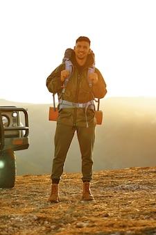 Retrato de um jovem viajante em equipamento de caminhada em pé perto de seu carro off-road