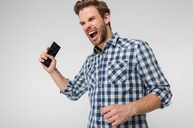 Retrato de um jovem zangado vestindo uma camisa xadrez, gritando e segurando o celular isolado na parede branca