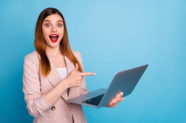 Retrato de um laptop animado e chocado apontando o dedo indicador impressionado