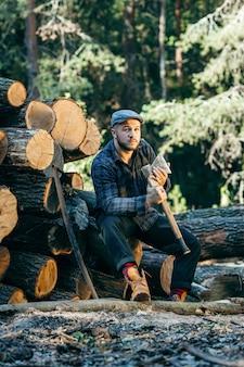 Retrato de um lenhador barbudo e brutal segurando um machado