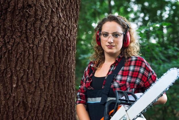 Retrato de um lenhador em pé perto do tronco de uma árvore na floresta segurando uma serra elétrica