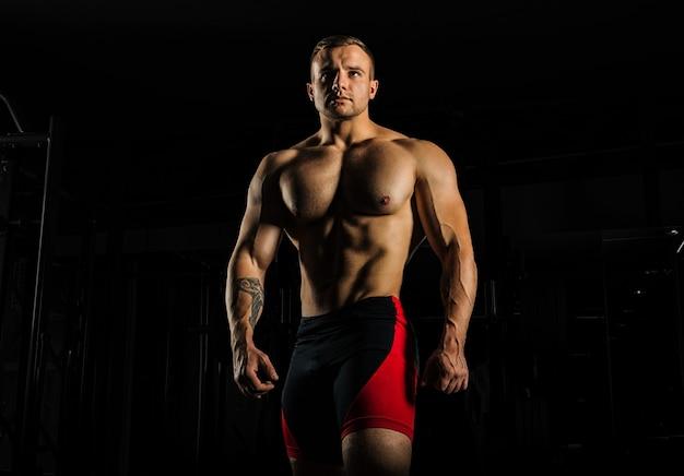 Retrato de um levantador de peso que posa sem camisa.
