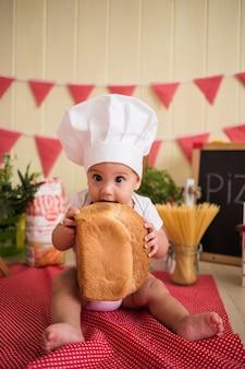 Retrato de um lindo bebê com um chapéu branco de chef comendo pão