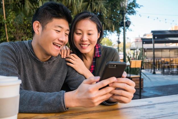 Retrato de um lindo casal asiático olhando para o celular enquanto está sentado e passando um tempo no café