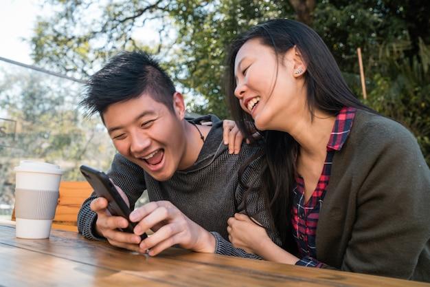 Retrato de um lindo casal asiático, olhando para o telefone celular enquanto está sentado e passando o tempo no café. conceito de amor e tecnologia.