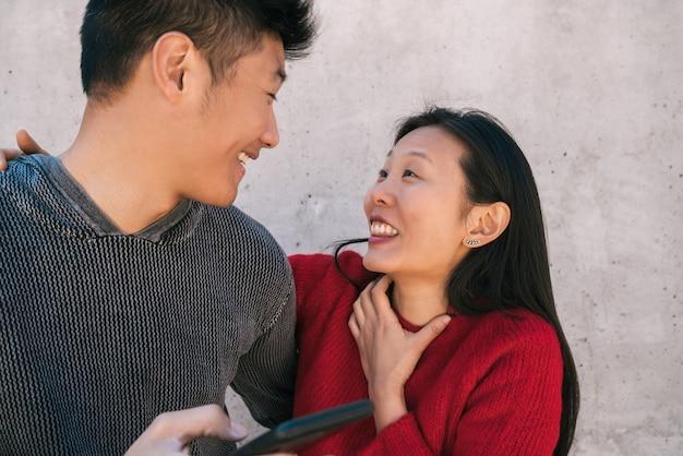 Retrato de um lindo casal asiático, olhando para o telefone celular, enquanto passam bons momentos juntos. conceito de amor e tecnologia.