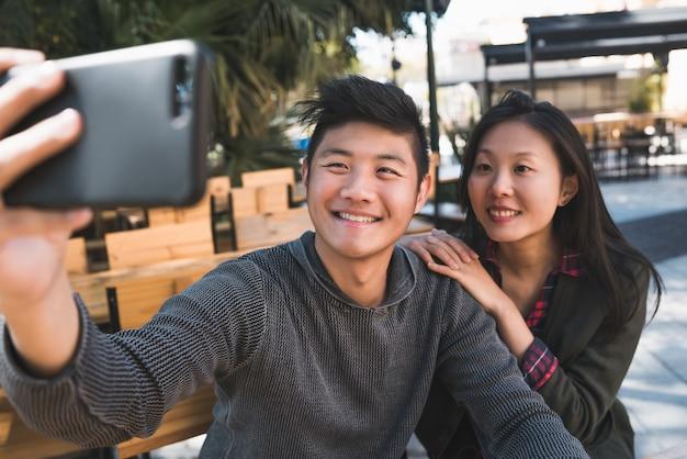 Retrato de um lindo casal asiático, se divertindo e tirando uma selfie com o celular na cafeteria.