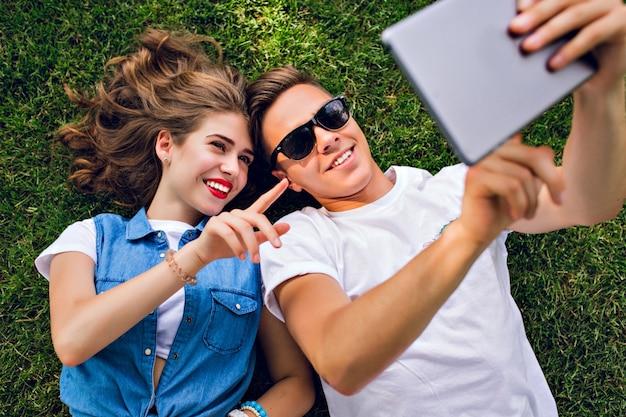 Retrato de um lindo casal de jovens deitado na grama do parque. cara de camiseta branca detém a sobrecarga do tablet, garota com cabelo longo cacheado com grande sorriso mostra no tablet.