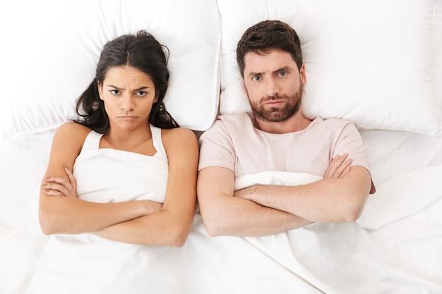 Retrato de um lindo casal jovem, deitado na cama, vista de cima, discutindo