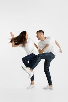 Retrato de um lindo casal jovem isolado na parede branca do estúdio