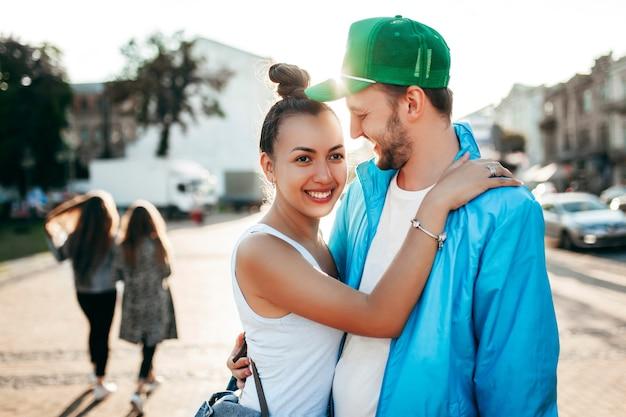 Retrato de um lindo casal jovem se beijando e se abraçando no telhado na luz do sol