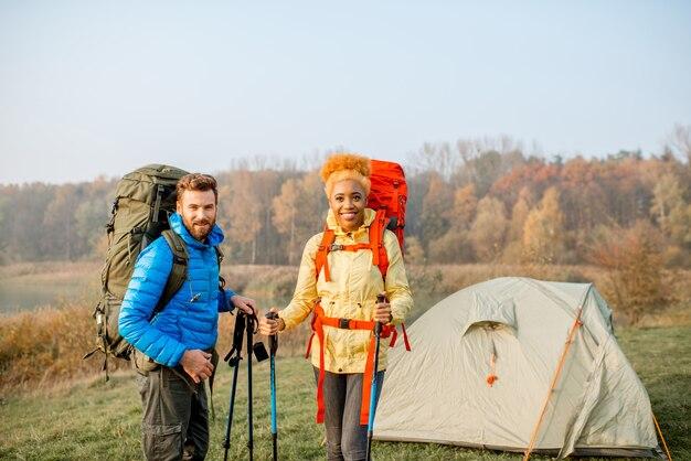 Retrato de um lindo casal multiétnico caminhando com mochilas e gravetos em pé no acampamento perto da barraca no gramado verde durante o outono