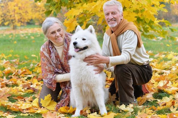 Retrato de um lindo casal sênior caucasiano com cachorro no parque outono
