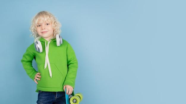 Retrato de um lindo garotinho caucasiano isolado na parede azul