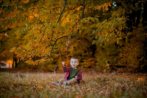 Retrato de um lindo garotinho sorridente no parque outono.