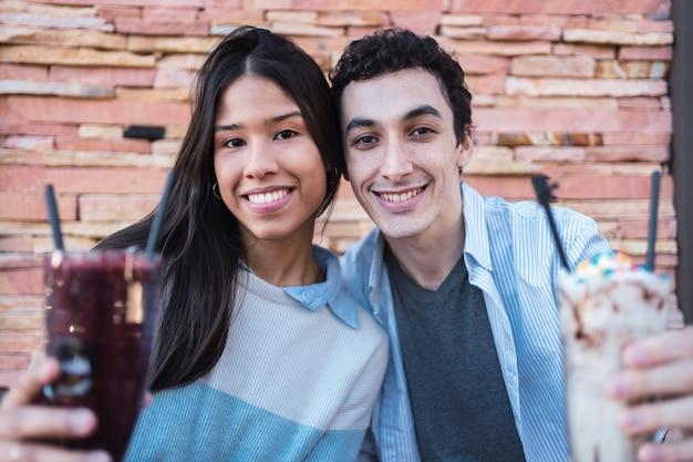 Retrato de um lindo jovem casal latino em um bar.