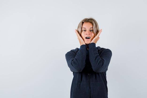 Retrato de um lindo menino adolescente com as mãos nas bochechas com capuz e olhando animado para a frente