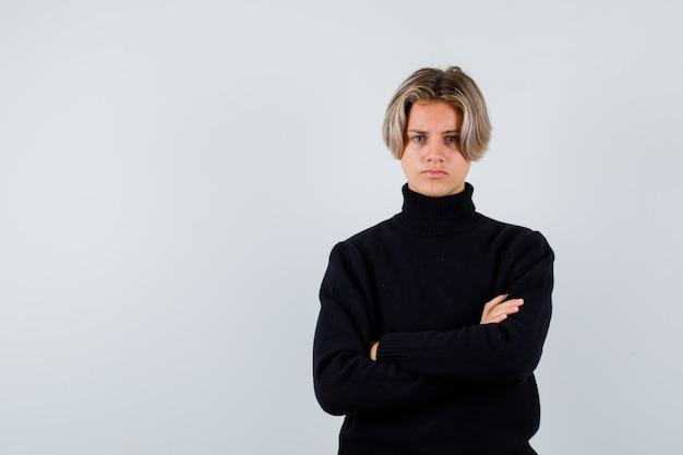 Retrato de um lindo menino adolescente com os braços cruzados em uma blusa de gola alta preta e uma vista frontal rancorosa