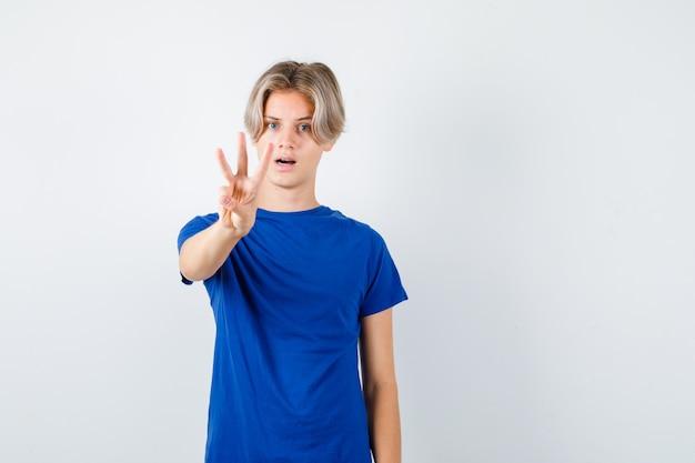 Retrato de um lindo menino adolescente mostrando três dedos em uma camiseta azul e olhando a vista frontal hesitante