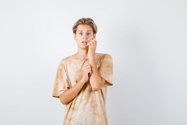 Retrato de um lindo menino adolescente segurando a bochecha com a mão na camiseta e olhando assustado para a frente