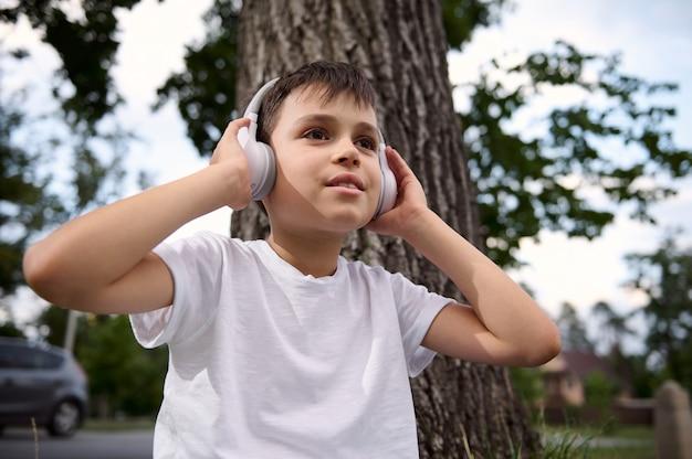 Retrato de um lindo menino adorável criança, usando fones de ouvido sem fio e curtindo música, descansando durante o recreio entre as aulas no parque público da cidade, após seu primeiro dia na escola