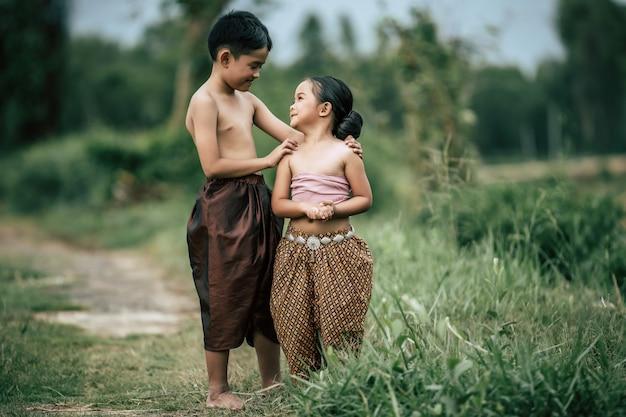Retrato de um lindo menino asiático sem camisa e uma menina em um vestido tradicional tailandês e colocar uma linda flor em sua orelha, em pé de mãos dadas e olhando para o céu com um sorriso, copie o espaço