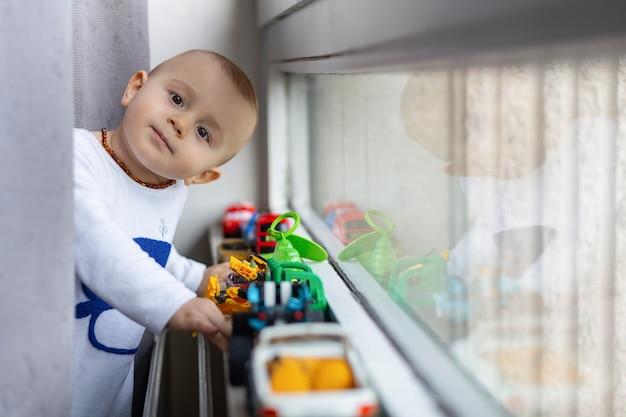 Retrato de um lindo menino brincando com brinquedos de plástico, ficando perto do peitoril da janela na sala