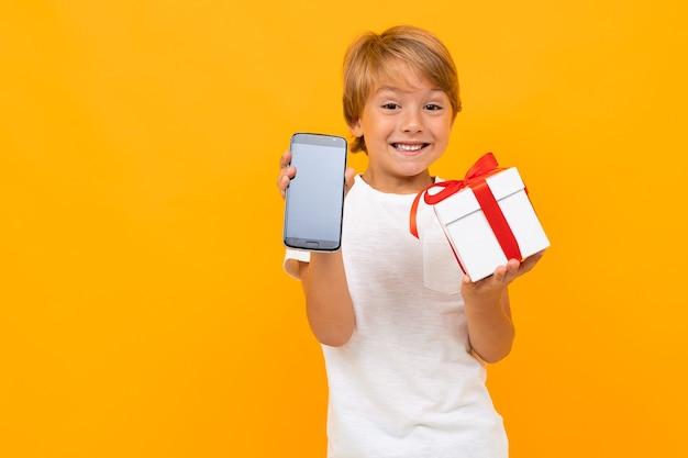 Retrato de um lindo menino caucasiano com camiseta branca e calça cinza segurando uma caixa branca com um presente e fazer selfie