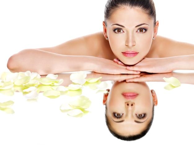 Retrato de um lindo rosto de uma jovem bonita com uma pele saudável e reflexos de flores cor de rosa em um espelho