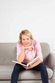Retrato, de, um, loiro, mulher madura, sentar sofá, segurando caneta, e, livro, contra, branca, fundo