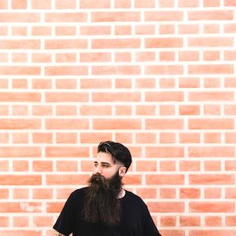 Retrato, de, um, longo, homem barbudo, frente, parede tijolo