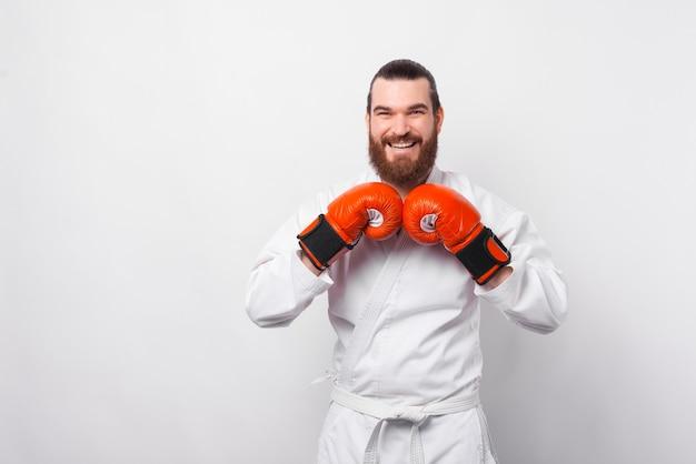 Retrato de um lutador de taekwondo sorridente usando luvas de boxe vermelhas