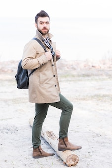 Retrato, de, um, macho, hiker, com, seu, mochila, ficar, com, seu, pé, ligado, registro