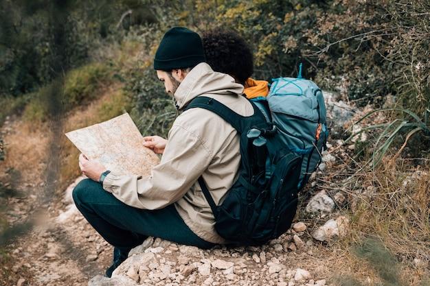 Retrato, de, um, macho, hiker, olhando mapa, sentando, com, seu, amigo