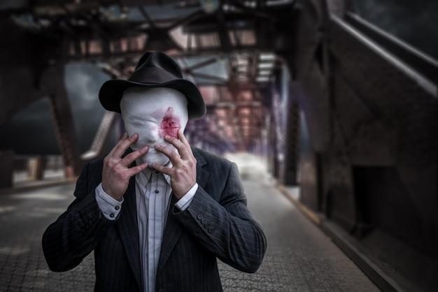 Retrato de um maníaco em série com o rosto envolto em bandagens ensanguentadas, conceito de assassino louco, assassino psicopata, perigo de crime e violência