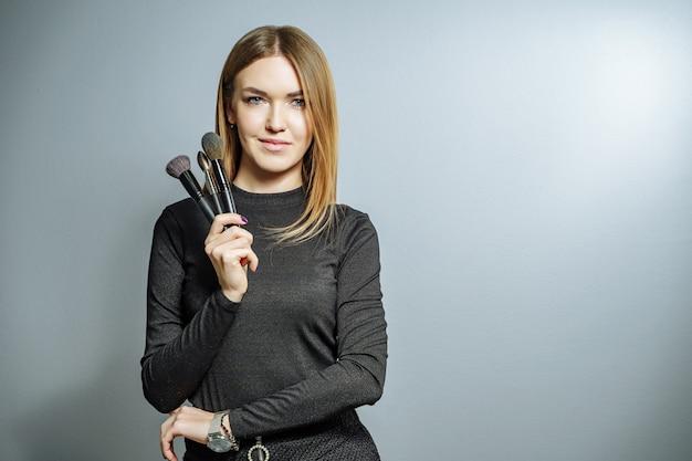 Retrato de um maquiador de mulher com o pincel de maquiagem em um cinza.