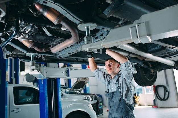 Retrato de um mecânico consertando um carro levantado