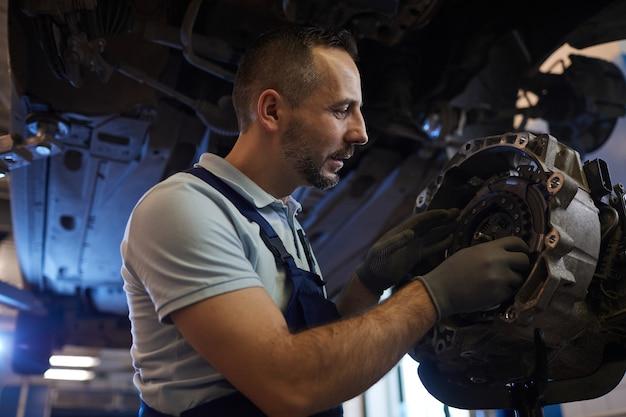 Retrato de um mecânico de automóveis barbudo consertando a caixa de câmbio em uma oficina automotiva, copie o espaço