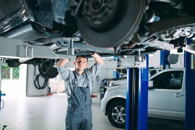 Retrato de um mecânico que repara um carro levantado.