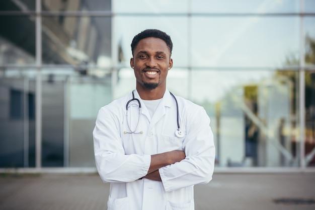 Retrato de um médico africano olhando para a câmera e sorrindo em frente à clínica