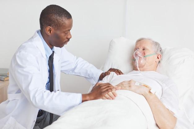 Retrato de um médico afro-americano cuidando de um homem idoso deitado em uma cama de hospital com máscara de suplementação de oxigênio, copie o espaço